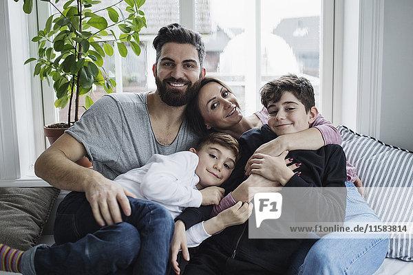 Porträt einer glücklichen Familie auf dem Sofa im heimischen Wohnzimmer