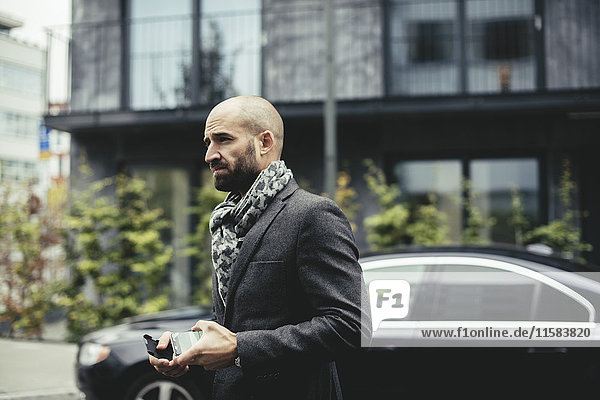Side view of mid adult businessman holding smart phone while walking on street