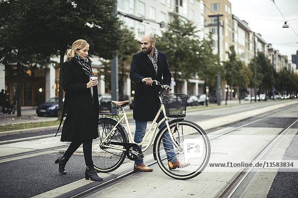 Volle Länge der Geschäftsleute mit Fahrrad über die Stadtstraße