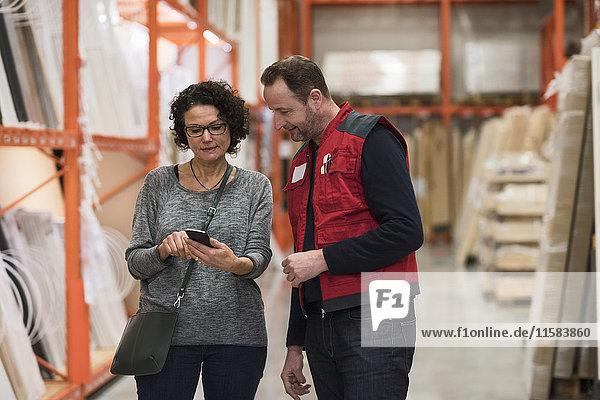 Verkäufer und Kundin mit Smartphone im Baumarkt