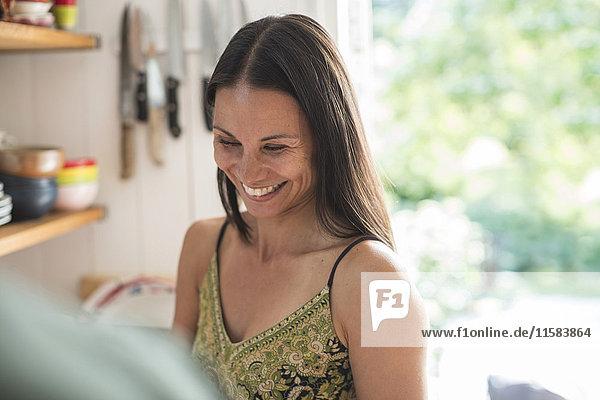Fröhliche Frau in der Küche zu Hause