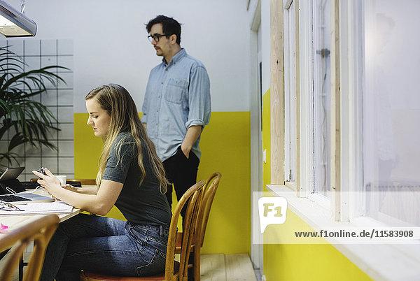 Junge Frau und Mann im Vorstandszimmer des Kreativbüros