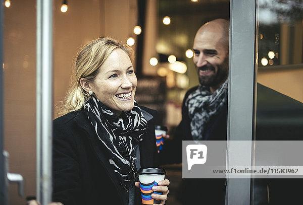 Lächelnde mittlere erwachsene Geschäftsfrau und Geschäftsmann beim Verlassen des Cafés