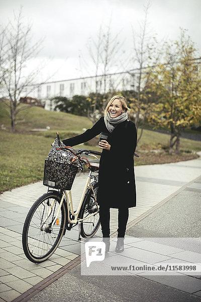 Volle Länge der fröhlichen mittleren erwachsenen Frau mit Fahrrad auf Fußweg