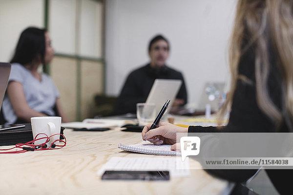 Mittelteil der jungen Frau  die am Schreibtisch schreibt  während die Kollegen im Hintergrund sitzen.