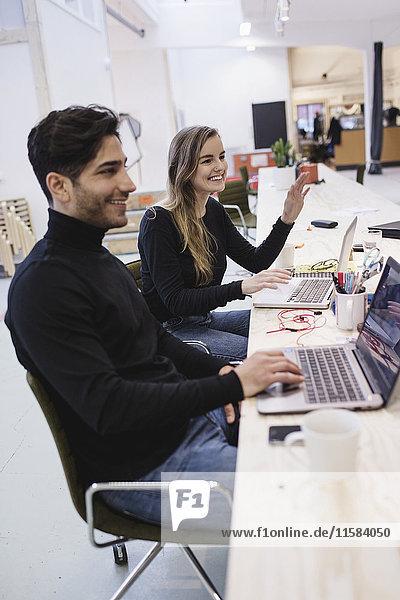 Fröhliche junge Frau und Mann schauen weg  während sie im Büro am Schreibtisch sitzen.