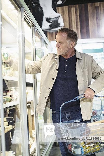 Reife Männer beim Einkaufen im Kühlregal im Supermarkt
