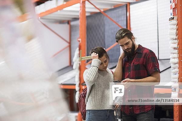 Pärchen mit Smartphone im Baumarkt