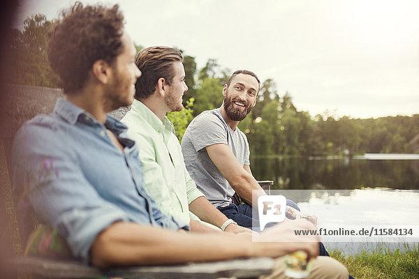 Fröhliche männliche Freunde beim Sitzen auf einer Holzbank am Seeufer