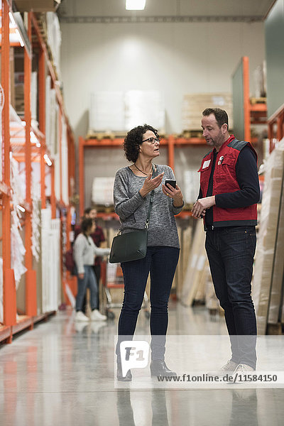 Female customer talking to salesman while holding smart phone in hardware store