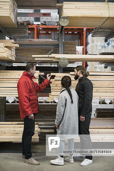 Verkäufer hilft dem Paar beim Kauf von Holzbohlen im Baumarkt