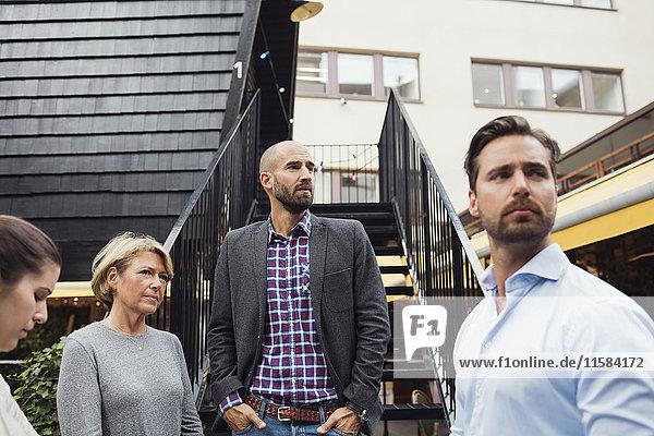 Geschäftsleute schauen weg  während sie vor dem Blockhaus stehen.