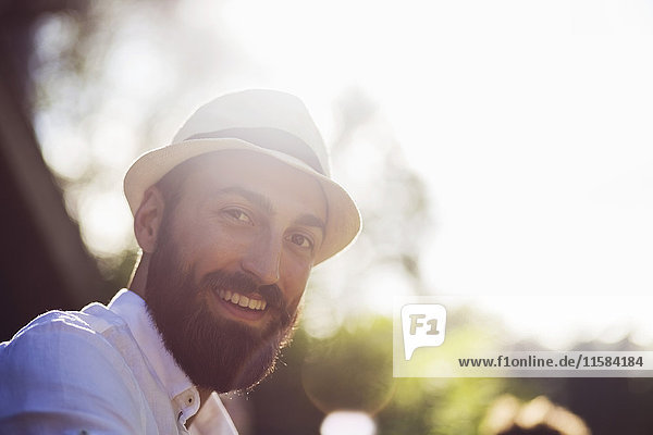 Porträt eines glücklichen Mannes mit Filzhut an einem sonnigen Tag.