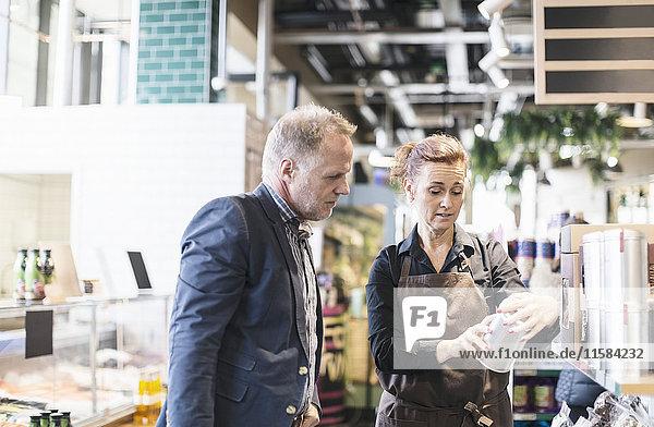 Verkäuferin erklärt Produkt dem Mann im Bio-Supermarkt