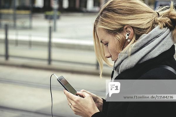 Seitenansicht der Geschäftsfrau mit Smartphone an der Straßenbahnhaltestelle