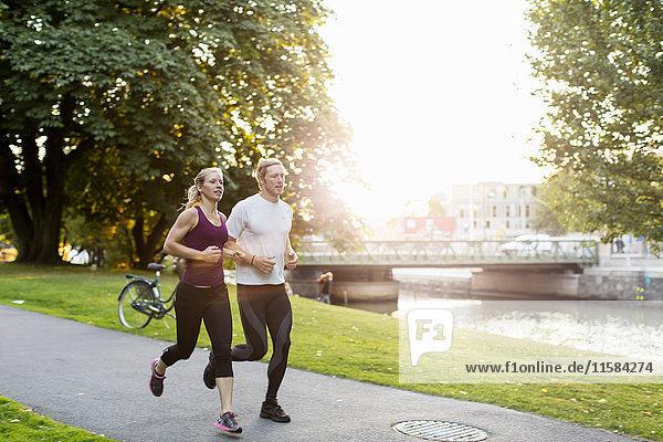 Paar Jogging auf dem Fußweg im Park bei Sonnenaufgang