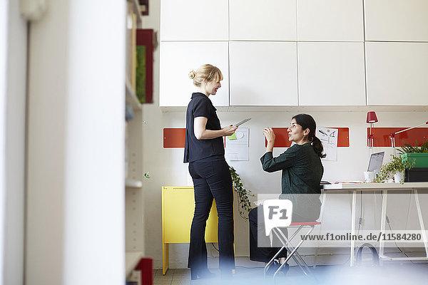 Volle Länge der mittleren erwachsenen Geschäftsfrau im Gespräch mit Kollegen im Büro