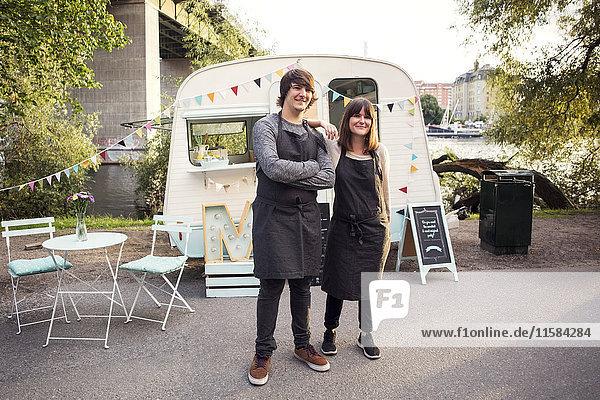 Vollständiges Porträt von selbstbewussten Besitzern  die auf der Straße gegen den Food-Truck stehen.