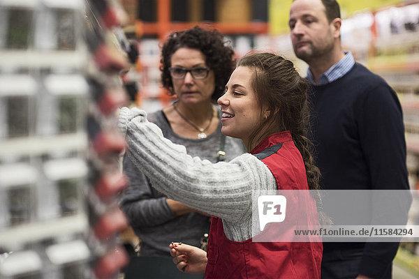 Seitenansicht einer lächelnden Verkäuferin  die ein reifes Paar im Baumarkt unterstützt.