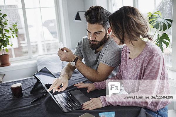 Mann zeigt auf Laptop auf Tisch im Wohnzimmer
