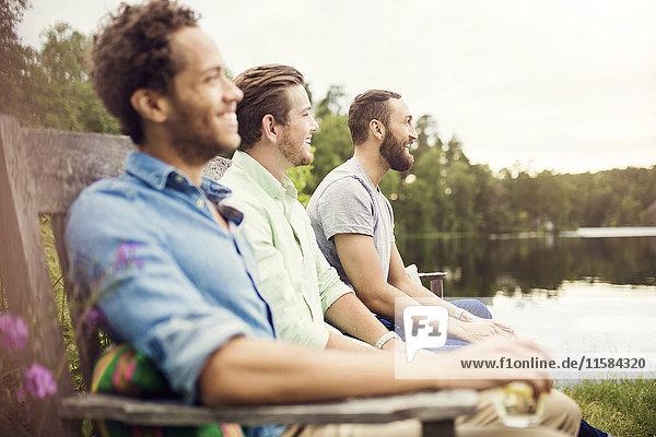 Glückliche Freunde sitzen auf einer Holzbank am Seeufer