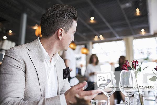 Geschäftsmann schaut weg  während er sein Handy im Restaurant hält.