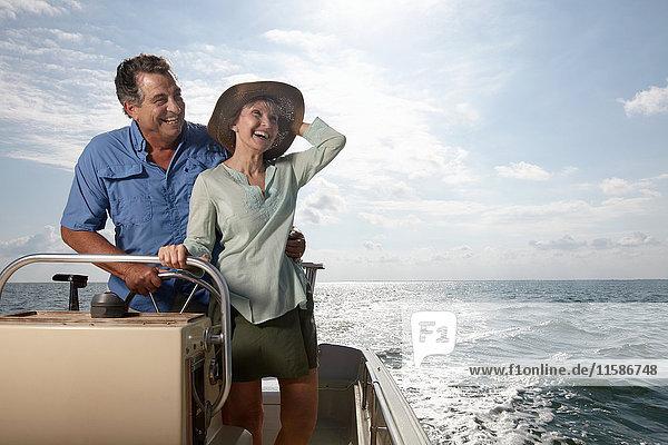 Älteres Ehepaar am Steuer eines Motorbootes
