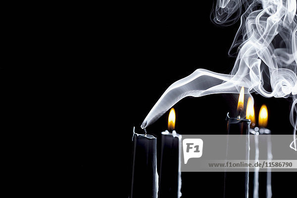Nahaufnahme einer rauchenden schwarzen Kerze