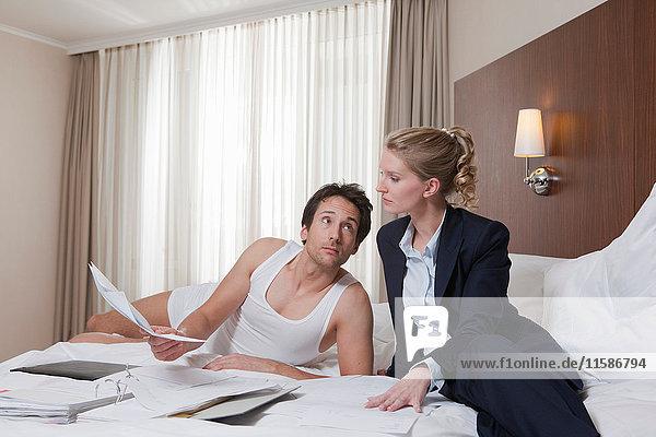 Paar auf Hotelbett beim Papierkram