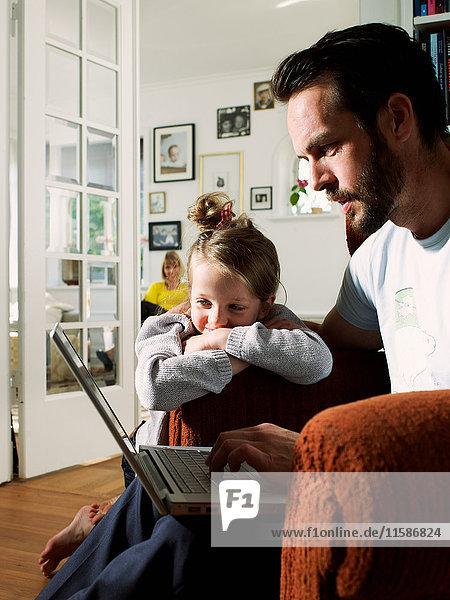 Älterer Mann mit Laptop im Sessel