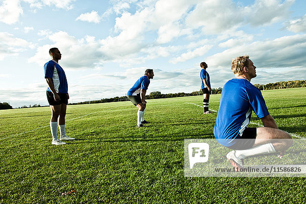 Soccer players standing on pitch