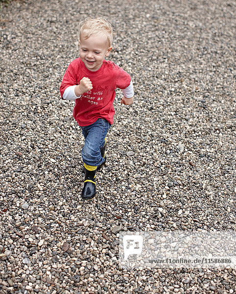 Toddler boy running on gravel