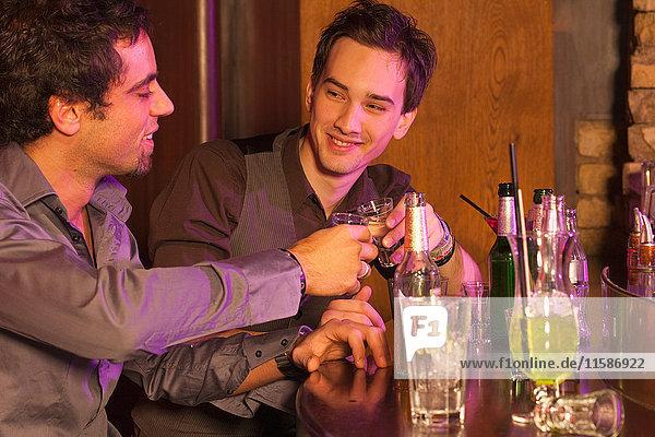 zwei Jungen in einer Bar  die ihr Glas erheben