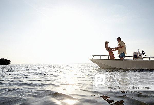 Senior couple holding hands on motorboat