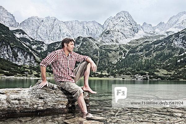 Mann mit baumelnden Füßen im See