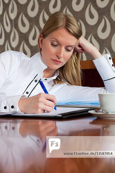 Frau studiert im Cafe
