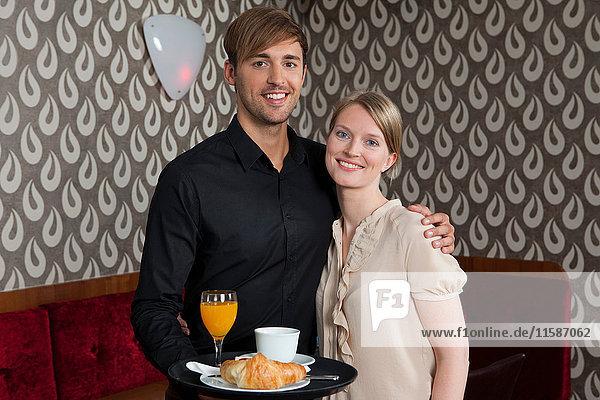 Kellner mit Tablett einer Frau  die das Essen umarmt