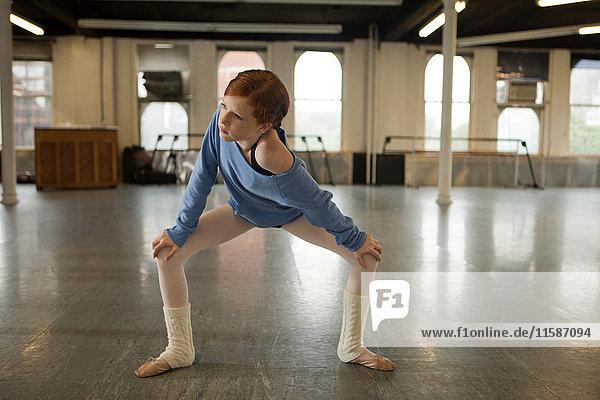 Ballet dancer warming up in dance studio