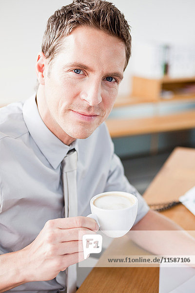 Man looking at viewer drinking coffee