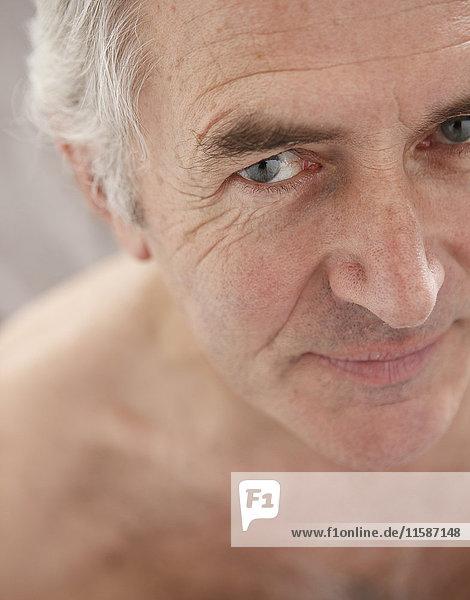 Älterer Mann lächelt und schaut in die Kamera