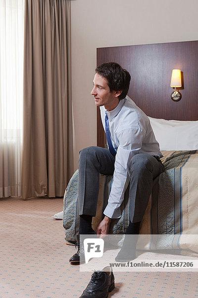 Geschäftsmann im Bett  der seine Schuhe anzieht