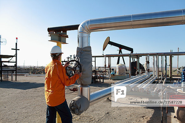 Worker adjusting pipes at oil field