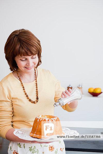 Frau in der Küche bereitet Kuchen zu