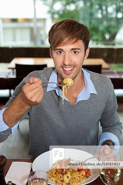 Man eating pasta in restaurant