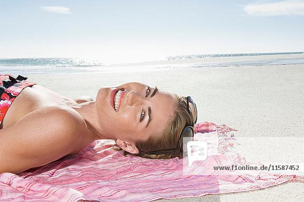 Eine am Strand liegende Frau lächelt