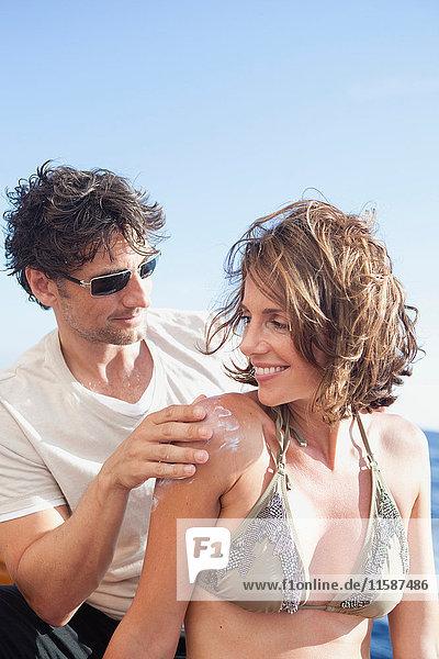 lachendes Paar beim Auftragen von Sonnencreme