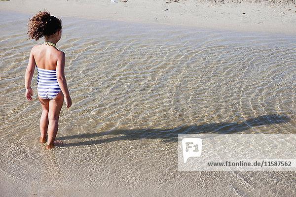 junges Mädchen spielt am Strand im Wasser