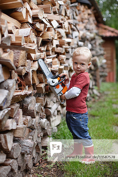 Kleinkind benutzt Spielzeugkettensäge im Freien