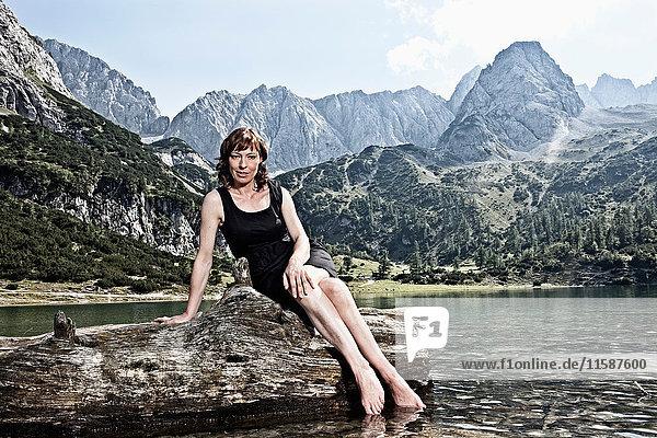 Frau baumelt mit den Füßen im See