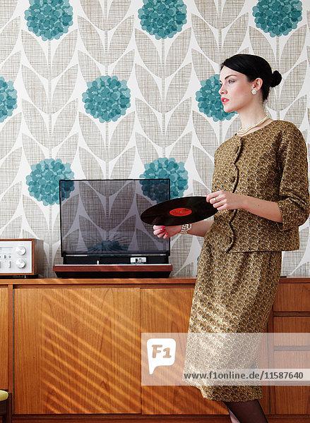 Frau in Vintage-Kleid mit Vinyl-Schallplatte